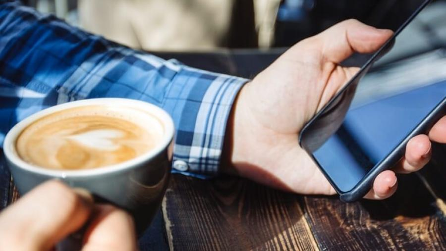 Hand holding a phone and a coffee