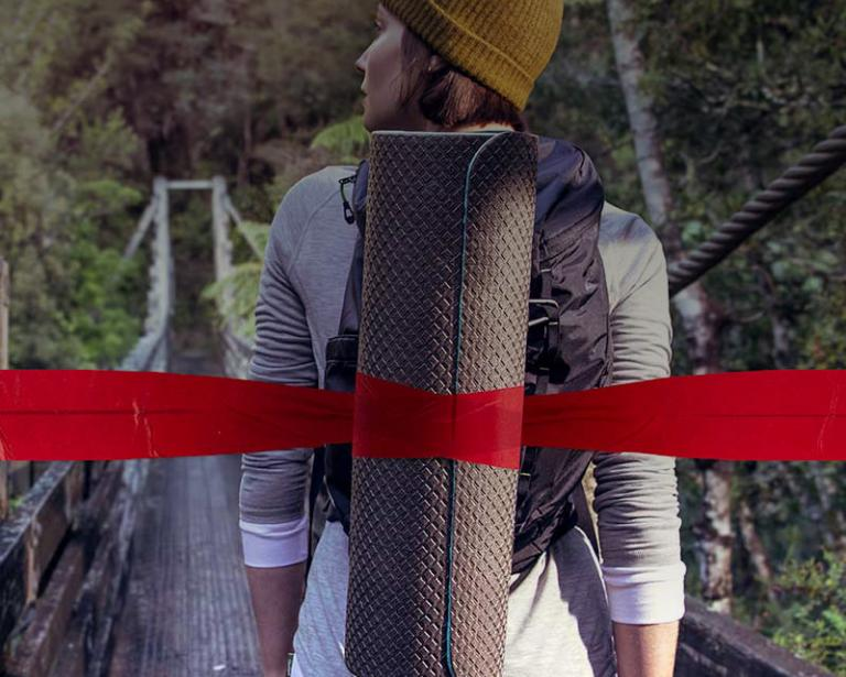 Woman crossing a wooden bridge over a gully in a forest with a backpack and camping supplies.  A red ribbon runs across the image and around her camping supplies.