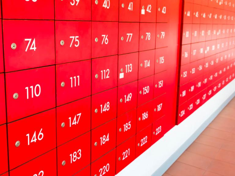 A wall of stacked red post office boxes or lockers with white numbering.
