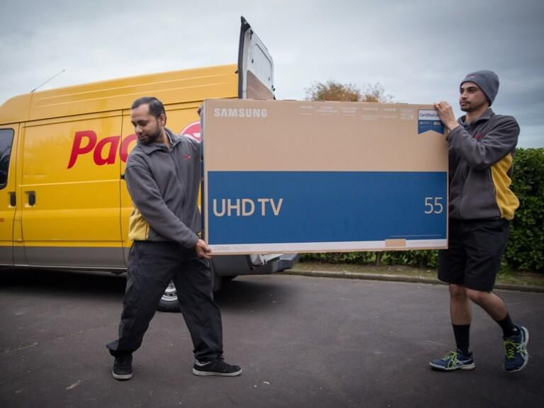 Two uniformed Pace couriers carrying a 55 inch TV in front of a signwritten Pace van