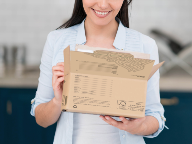 Woman holding a recyclable cardboard box. Gen Less logo appears on bottom left