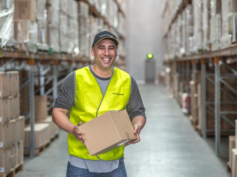 Smiling manager wearing a high visibility vest, holding a cardboard box in a warehouse aisle with stacked shelves.