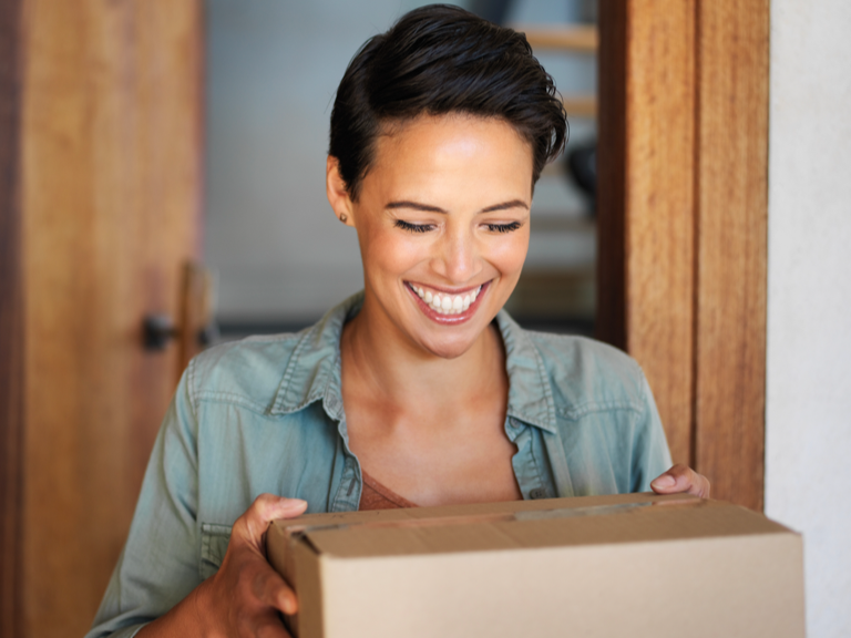 Smiling woman in her doorway receiving a parcel in a cardboard box.