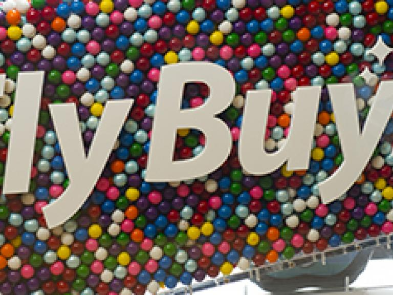 Fly Buys logo on a background of multi-coloured marbles.