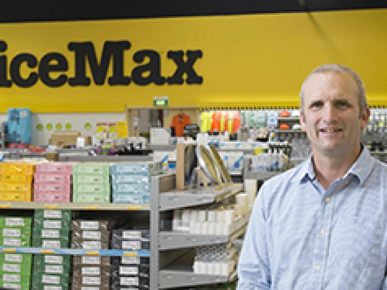 Business-man standing in an OfficeMax store with shelves stacked with stationery behind him.