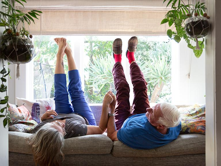 older couple sitting on their couch upside down, feet in the air