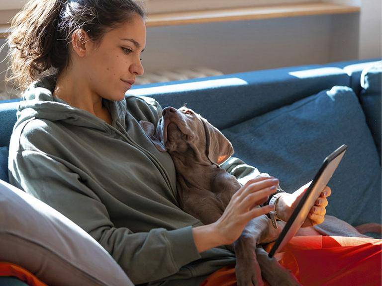 young woman on a sofa with a dog and smartphone
