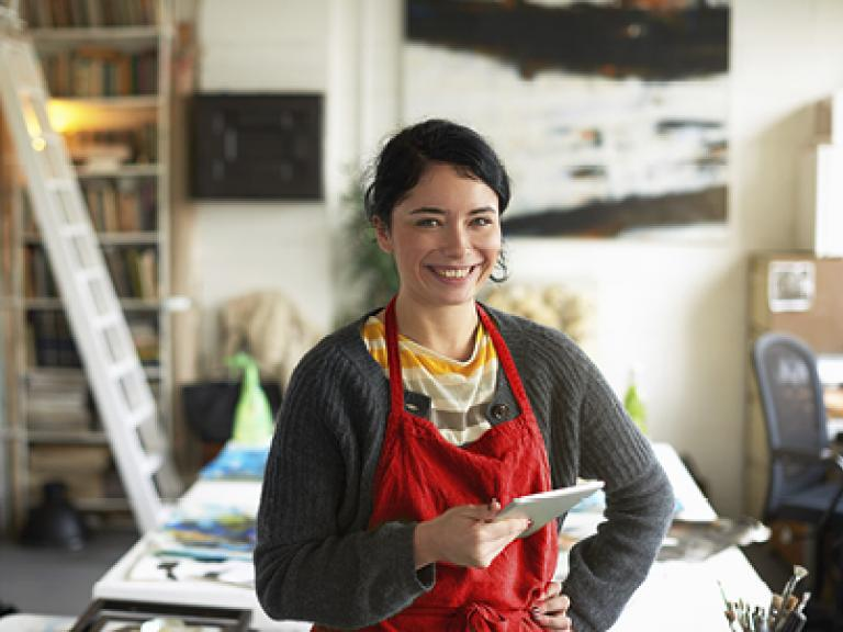 smiling young woman artist in her studio holding a digital tablet